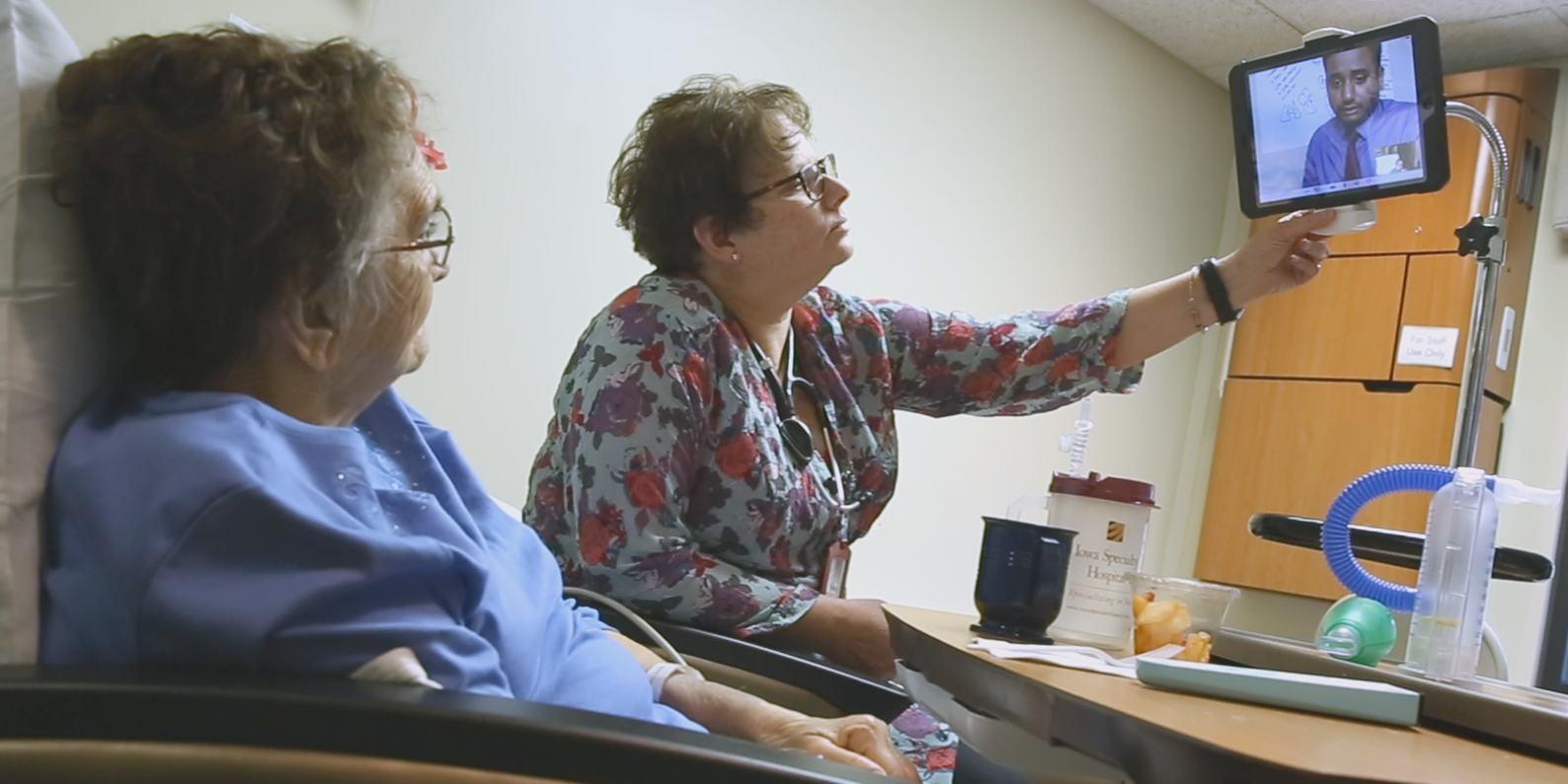Patient visiting with onsite provider and virtual hospitalist via computer