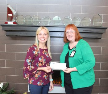 Abby Young is presented with IHERF scholarship check from Amy McDaniel, Iowa Specialty Hospital – Belmond CEO.