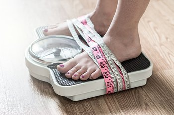 Feet tied to a scale with multiple tape measures