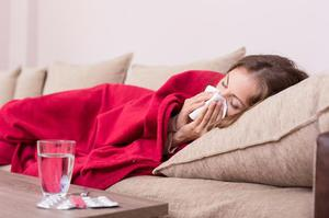 Woman lying on couch with blanket; has influenza; blowing nose with tissue