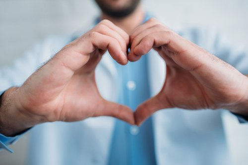 Man holding up his hands in heart shape.
