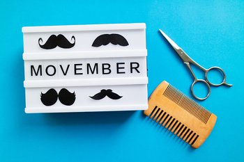 Sign with 4 moustache shapes saying Movember and scissors and comb beside it.