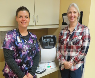 Fawn Roberts and Dawn Korf, Iowa Specialty Hospital employees, show off a new vision screener made possible in part from the Wright County Charitable Foundation.