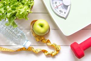 Salad, water bottle, apple, hand weight, body scale, and tape measure